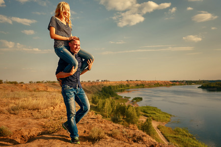 carrying girl: Loving couple on the river bank. Man carrying girl on piggyback. Summer day. The concept of a romantic relationship.