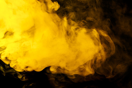 black smoke: Abstract yellow hookah smoke on a black background. Photographed using a gel filter. Texture. Design element.