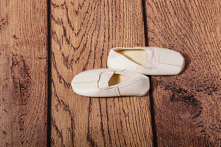 choreographic: The third ballet position. Children Gym shoes on a wooden floor. The concept of classical ballet and modern dance. Stock Photo