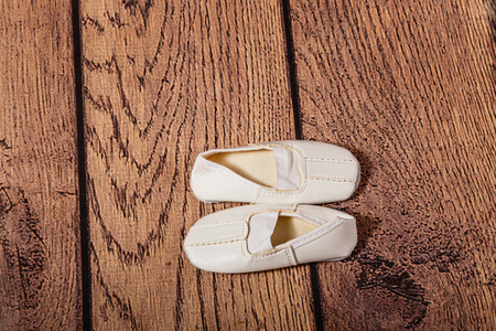 choreographic: The fifth ballet position. Children Gym shoes on a wooden floor. The concept of classical ballet and modern dance. Stock Photo