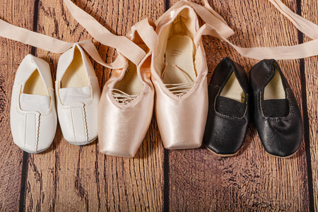 gym shoes: Ballet pointe shoes and childrens Gym shoes lie on the wooden floor. The concept of classical ballet and modern dance. Shot close-up.