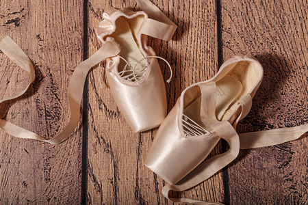ballet slipper: Ballet pointe shoes lie on the wooden floor. Vintage. The concept of classical ballet and modern dance.