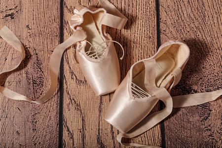 ballet slippers: Zapatillas de punta de ballet se encuentran en el piso de madera. Vendimia. El concepto de ballet cl�sico y danza moderna. Foto de archivo