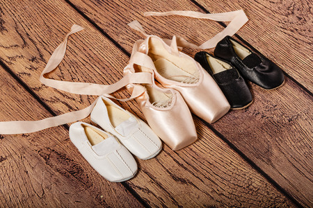 gym shoes: Ballet pointe shoes and childrens Gym shoes lie on the wooden floor. The concept of classical ballet and modern dance.