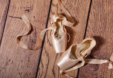 Ballerina: Ballet pointe shoes lie on the wooden floor. Vintage. The concept of classical ballet and contemporary dance. Shot close-up. Stock Photo