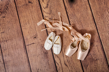 gym shoes: Ballet pointe shoes and white Gym shoes lie on the wooden floor. The concept of classical ballet and modern dance. Shot close-up.