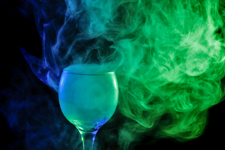 drinks: Abstract art. Hookah blue - green smoke in a cocktail glass on a white background. Witch potion background for Halloween. Unusual bar drink. Drink in the glass with the effect of dry ice. Stock Photo