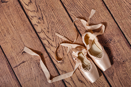Ballet pointe shoes lie on the wooden floor. Retro. The concept of classical ballet and modern dance. Shot close-up.