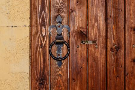 door bolt: Round metal door handle on a wooden door with bolt. Safety concept.