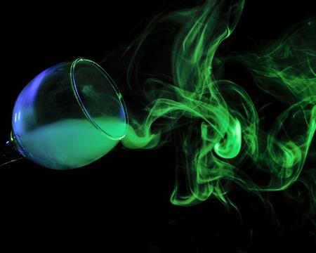 bruja: Arte abstracto. Azul Hookah - humo verde en una copa de cóctel sobre un fondo blanco. Bruja fondo poción para Halloween. Bebida bar inusual. Bebida en el vidrio con el efecto de hielo seco.
