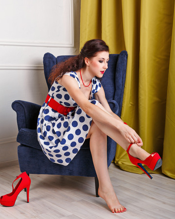 pinup girl: Pin-up girl in a fashionable dress clothes red high-heeled shoes. Stock Photo