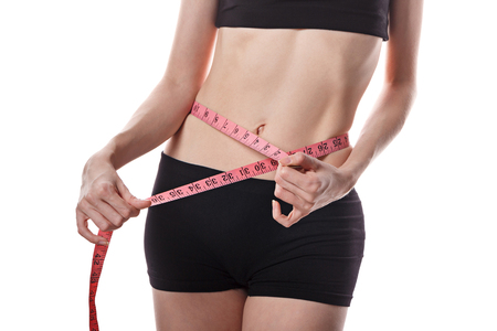 Young slim woman measures the waist. Isolated on white background. Person is unrecognizable. The concept of weight loss and healthy life. Stock Photo