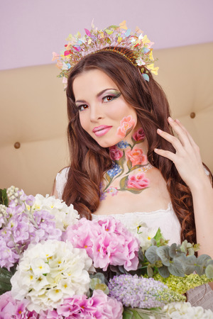 floristry: Young attractive girl with make-up floristry face art. The concept of genuine natural beauty. Stock Photo