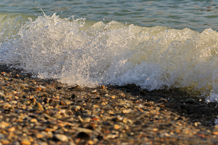 high tide: Sea surf at high tide on a pebble beach. Summer vacation. Travel concept to the sea.
