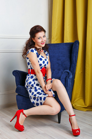pinup girl: Pin-up girl in a fashionable dress and red high heels sitting on a chair.