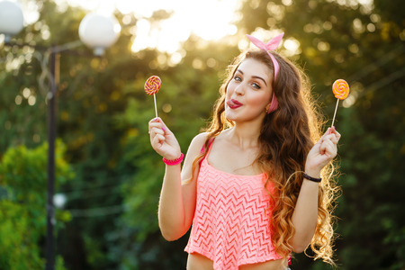 pinup girl: Hipster girl showing tongue and holding two lollipop. Photo at sunset. Warm toning. Concept Pin-up girl style. Soft focus.
