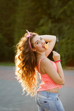 pinup girl: Hipster girl with a lollipop and long hair. Photo at sunset. Warm toning. Concept Pin-up girl style. Soft focus.