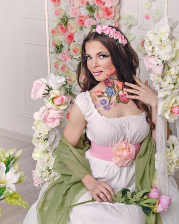 floristry: Young attractive girl with make-up floristry face art. Portrait of a girl holding a rose and straightens her hair. The concept of genuine natural beauty. Stock Photo