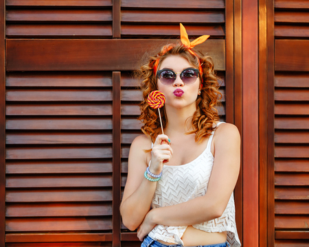pinup girl: Hipster girl in sunglasses is holding a lollipop. Girl sends an air kiss. Concept Pin-up girl style. Soft focus.
