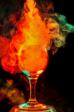 Abstract art. Hookah smoke in orange cocktail glass on a white background. Witch potion background for Halloween. Unusual bar drink. Drink in the glass with the effect of dry ice.