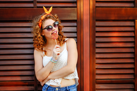 playfulness: Hipster girl in sunglasses licking a lollipop. Concept Pin-up girl style. Soft focus.