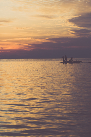 big game: Big Game Fishing at sunset. Landscape of the ocean and sunset in the clouds. Unrecognizable people silhouettes. The concept of rest. Stock Photo