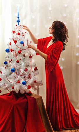 decorates: Lovely girl decorates the Christmas tree. The girl in the red dress. Merry Christmas.