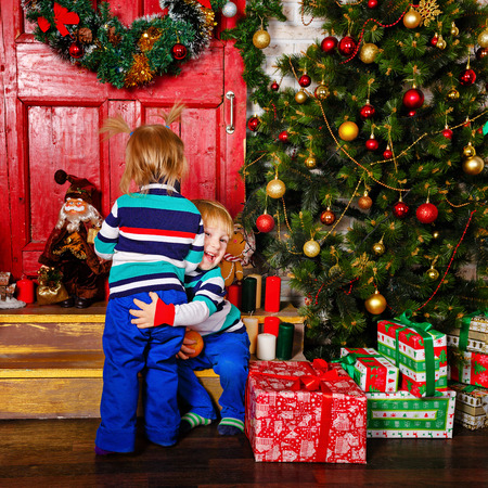 innocent girl: Brother hugging his sister near a Christmas tree. Cute little kids. Happy family and Merry Christmas. Stock Photo