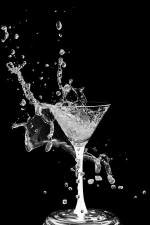 Abstract art. Cocktail glass with splashes of liquid isolated on a black background. Alcoholic cocktail. Quench your thirst. Cocktail party. Standard-Bild