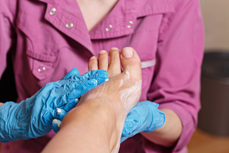 chiropodist: Master chiropody doing massage and apply the scrub. Spa. Concept body care.