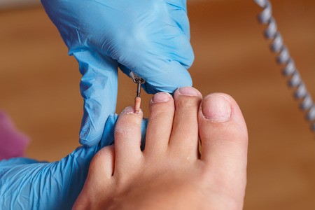 chiropodist: Master pedicure shapes the nails and cuticles. Hardware manicure. Concept body care. Stock Photo