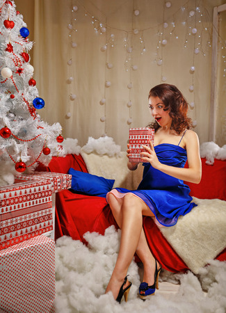 female christmas: Lovely girl lays gifts near a Christmas tree. Girl in a blue dress. Merry Christmas.