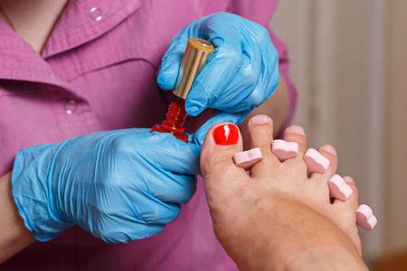 chiropody: Master chiropody applying gel nail polish. Spa. Concept body care.