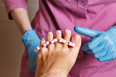 chiropodist: Master chiropody rubbing alcohol, fingernails polish before applying the gel. Spa. Concept body care.