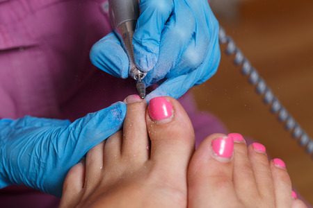 chiropodist: Master pedicure gel removes the old nail polish client. Secure hardware nail polish remover. Concept body care.