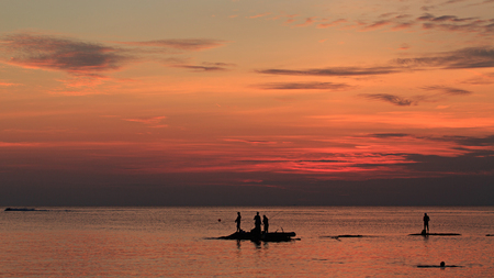 big game fishing: Big Game Fishing sunset. Landscape of the ocean and sunset in the clouds. Unrecognizable people silhouettes. Stock Photo