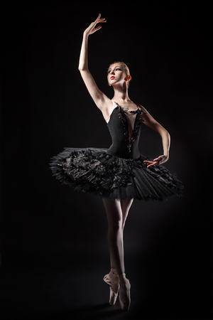 ballerina costume: Slim ballerina in a black corset and black tutu. Rehearsal in the theater. Classical Ballet.