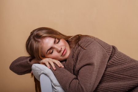 convalescence: Girl in a warm sweater leaning on the arm of the sofa. Girl fell asleep. Season colds. Home comfort. Knit garments. Expressive look. Convalescence.