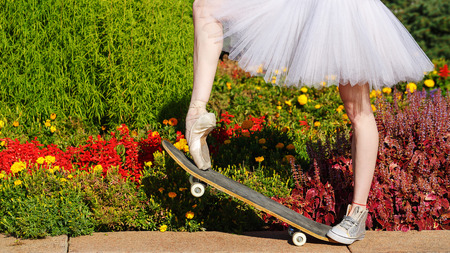 pointes: Legs of a ballerina on a skateboard. Feet shod in sneakers and pointes. Modern fashion. Photo closeup.