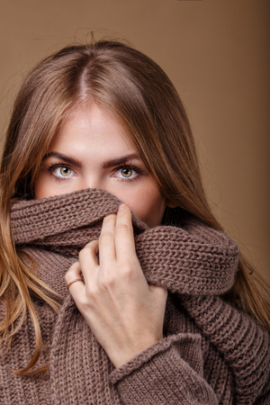 informal clothing: Girl hides her face in a warm sweater. The picture seen only beautiful eyes. Knit garments. Expressive look.