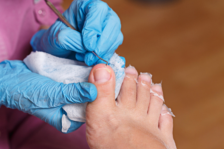 chiropodist: Master chiropody cleans fingernails. Spa. Concept body care. Stock Photo