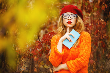 Lovely girl in a beret, sweater and glasses walking in autumn park, holding a notebook. The poet seeks inspiration. Girl enjoying fresh air. The girl white smile. The concept of modern youth fashion.