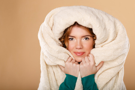 cold season: Beautiful young girl with curly hair wrapped in a warm blanket. The cold season. Home comfort.