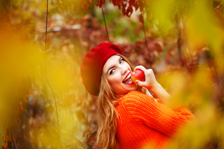 Pretty girl in a beret and a sweater in autumn park, holding a ripe apple and smiling. The girl bites ripe apple. The girl white smile. The concept of healthy teeth.