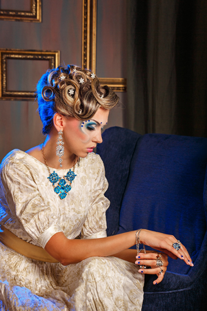 corrects: Young girl sitting in a chair. Girl dressed in evening dress. Face art and jewelry. The girl corrects a bracelet on her arm. The concept of high fashion. Stock Photo