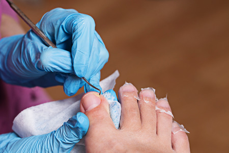 chiropody: Master chiropody cleans fingernails. Spa. Concept body care. Stock Photo