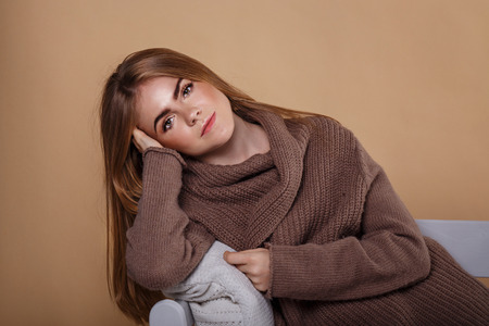 informal clothes: A girl in a warm sweater leaning on the arm of the sofa. Season colds. Home comfort. Knit garments. Expressive look. Convalescence.