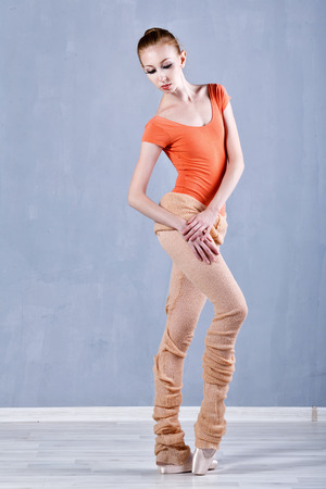 en pointe: Classical ballet performed by a slim ballerina. Girl rehearses dance. Stock Photo