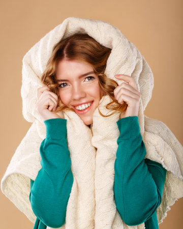 cold season: Beautiful young girl with curly hair wrapped in a warm blanket. The cold season. Homeliness. Foto de archivo