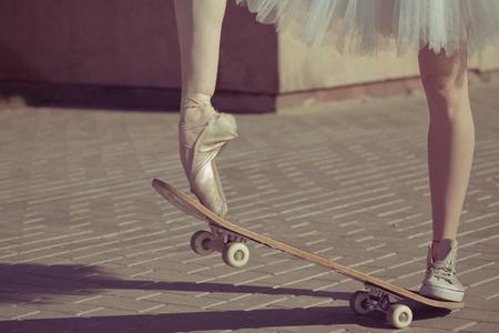 donna che balla: Le gambe di una ballerina su uno skateboard. Piedi calzati in scarpe da ginnastica e scarpe da balletto. Moda moderna. Foto primo piano. Archivio Fotografico